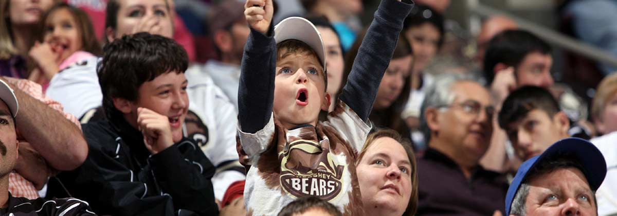 Young boy cheering in crowd with bears shirt